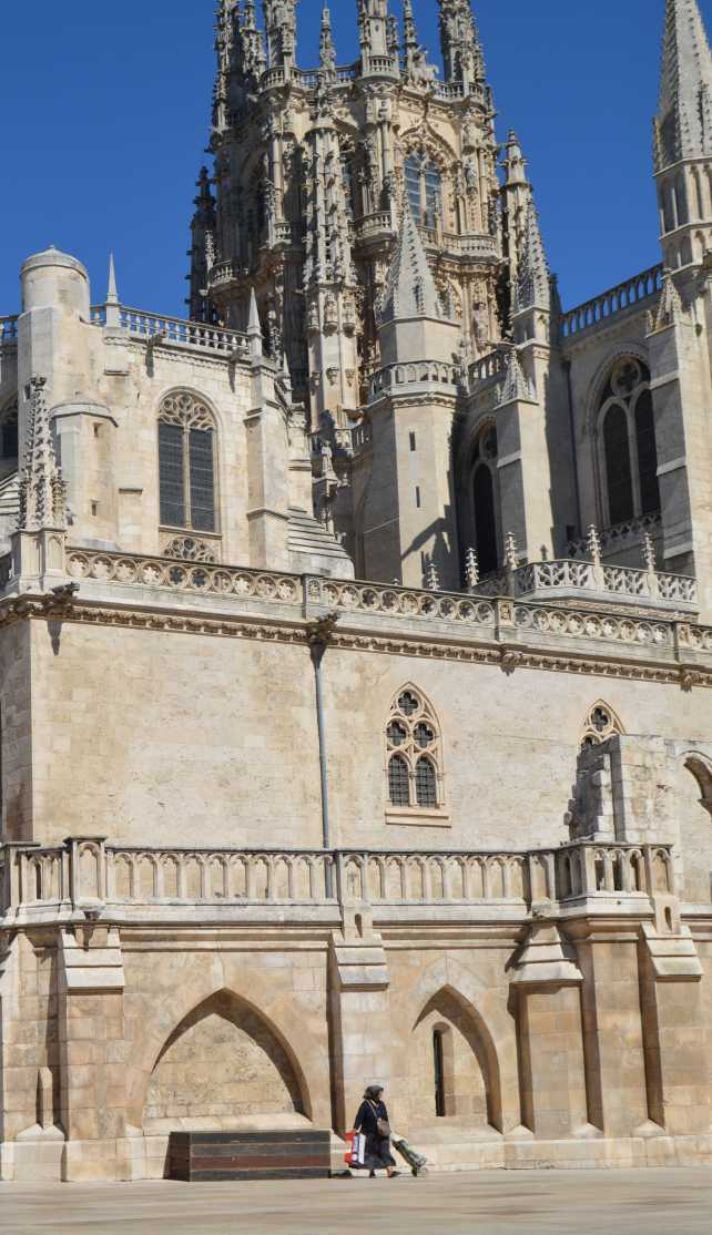 Beggar lady walks past Burgos Cathedral