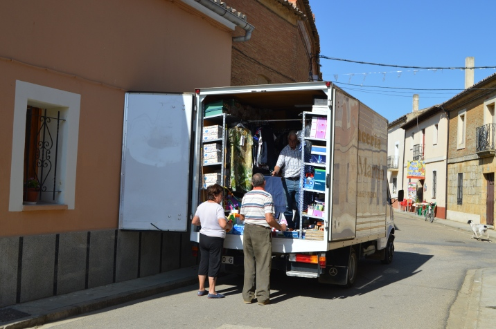 Trucks like these are important to residents on the Meseta. Here, the female customer buys cleaning detergent. The gentleman shops for trousers.